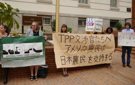 TPP交渉の日米閣僚協議が行われている会場前で、「日本の農家支持」をアピールする全米家族経営農場連合の人々=24日、ワシントン。※この記事の写真→ http://t.co/6O1pPUnfCA http://t.co/mfg6EDZ2WU