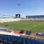 Gras wordt gemaaid in het zonovergoten GSP Stadion voor #apoaja. Uur voor de kick-off wordt nog gesproeid. #UCL.