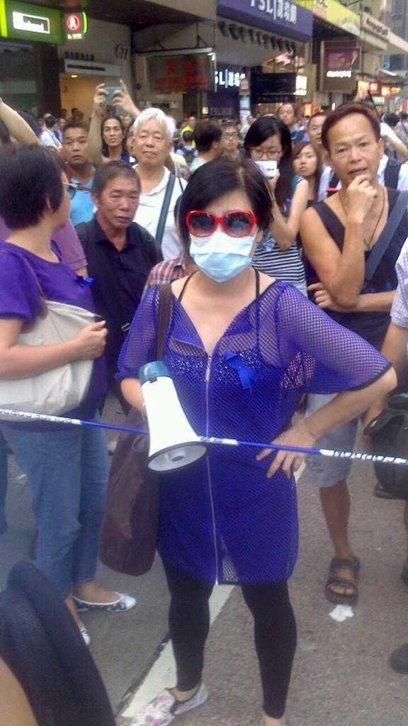 """圖中蒙臉手拿揚聲器的女人,就是帶頭襲擊旺角佔中示威者的人。 http://t.co/QhvJLCHtIy via @bryanhimself"""""""