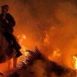 Daredevil revellers ride horses through flames during bizarre 'Luminarias' festival celebrating Spain's patron saint of animals