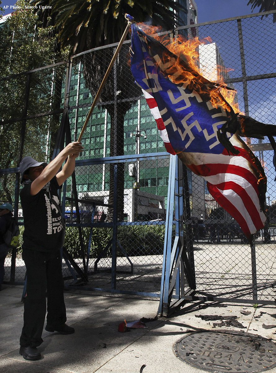 Protesters burn a mock American flag, with swastikas in place of stars, in front of the US Embassy in Mexico City on Friday.