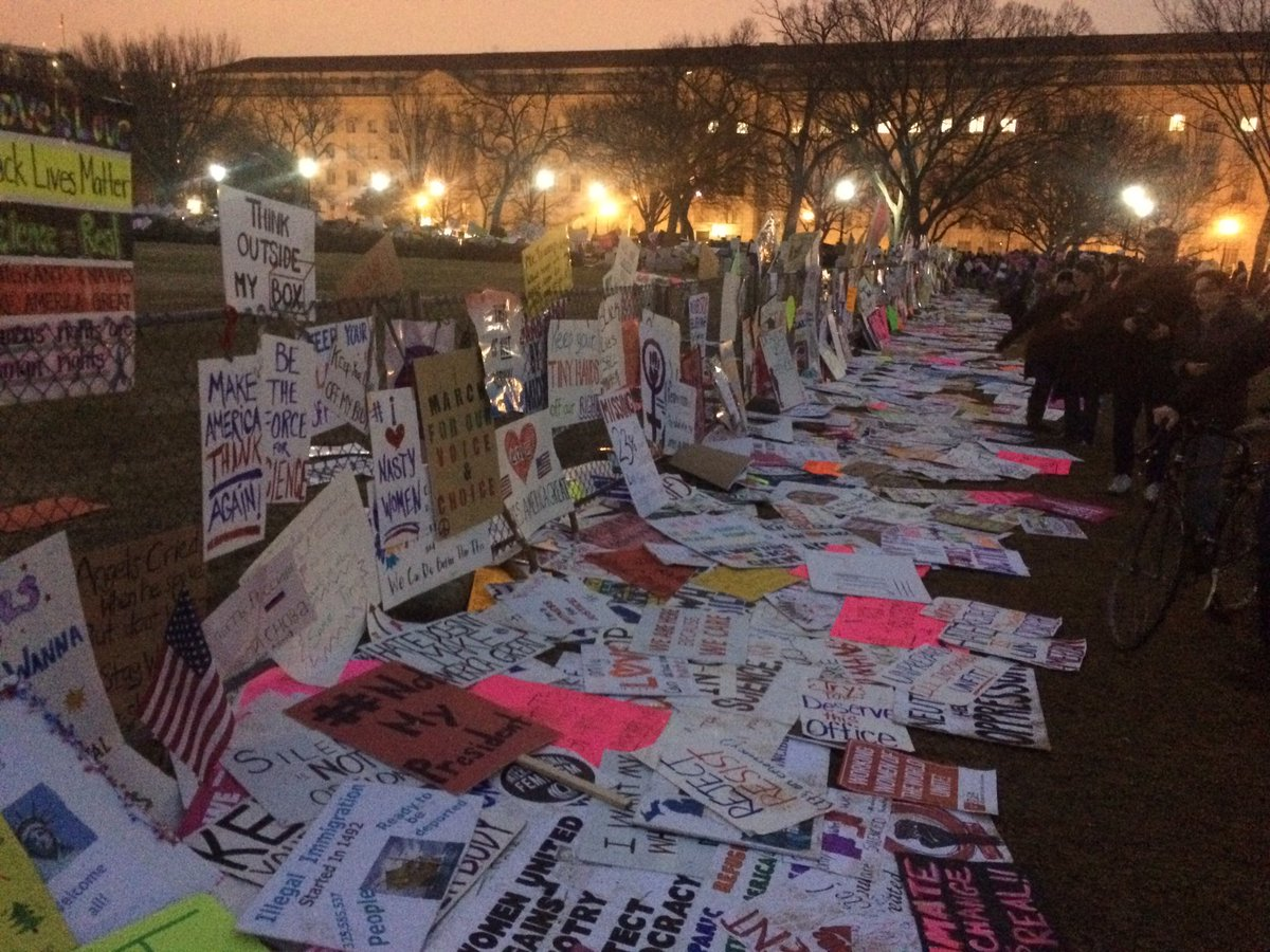 One of the Women's Marchers' final acts: leaving their protest signs in front of the White House.