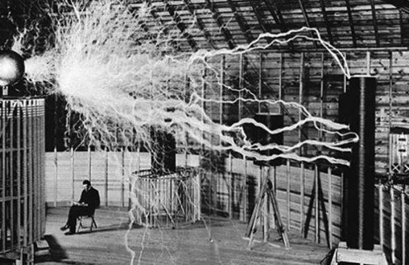 Nikola Tesla sentado en su laboratorio con su Magnifying Transmitter