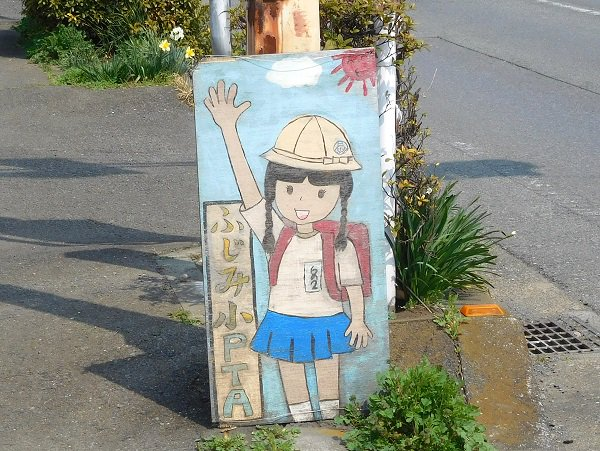飯能市の飛び出し少女 というより生徒に注意を促すという要素が強いのかな。ヤマノススメ第97号目のカットの横断歩道で