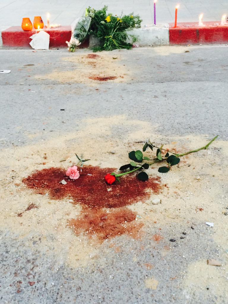 Surrounding the blood of the victims the croud lays down flowers and candles ##BardoAttack #Tunisia http://t.co/bPmIzRVaVv
