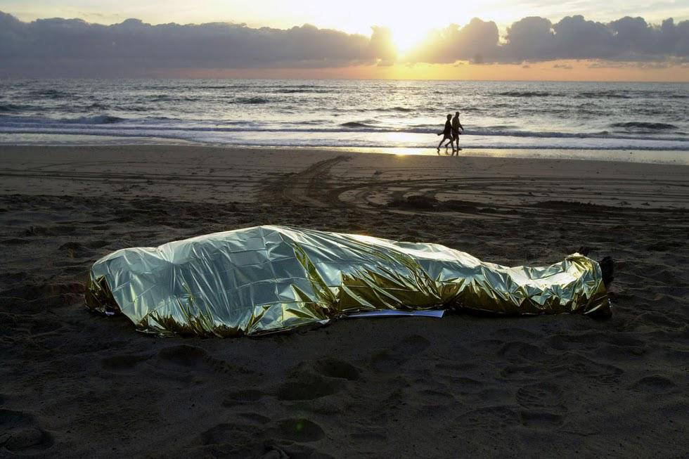 Immigrant's corpse in Fuerteventura, Spain, as beachgoers stroll by. By Juan Medina http://t.co/ottkeZZveN http://t.co/kCcyEno60N
