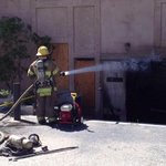 A #calfire firefighter hoses down a #deserthotsprings building that caught fire @MyDesert http://t.co/TgNWUgM9re