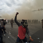 Gas mask on, fist in the air. Riot police behind plumes of smoke. (by AJ+s @Darielm) #BaltimoreRiots #FreddieGray http://t.co/wCbzkFc2Lq
