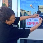 "Pratt CEO Carla Hayden welcoming folks and placing a ""Were OPEN"" sign at the Pennsylvania Ave Branch. http://t.co/p3aA9VufBo"