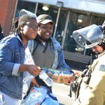 Women hand out water, Frosted mini wheats to police guarding W Balt near the burned out CVS #baltimoreriots http://t.co/XnQatpcFwa