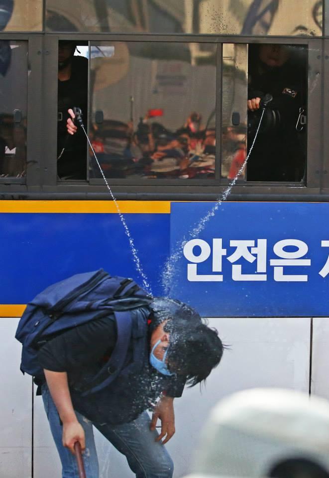 경찰 둘이 한 사람을 정조준 해 캡사이신액을 쏘고 있다. 사진. 이정용. 2015년 5월 1일 서울 공평동.  https://t.co/apjV4BxkZI http://t.co/fpwbeMopMg