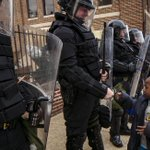 Young boy fist bumps riot cop in #Baltimore (photo by Lucas Jackson) http://t.co/QM6peu3gff