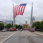 Firefighters raise an American flag over 10th and Douglas Streets along the funeral route. http://t.co/6kU07g2zQ2