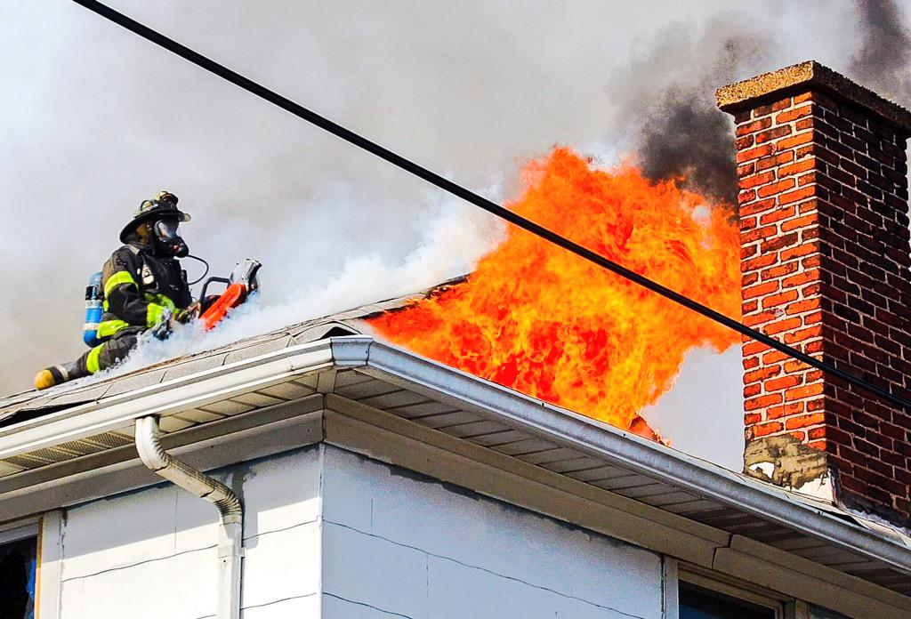 Great shot of a member working on opening up a roof this afternoon on the 4 Alarm fire in Curtis Bay #Baltimore http://t.co/WB86Tb74G9
