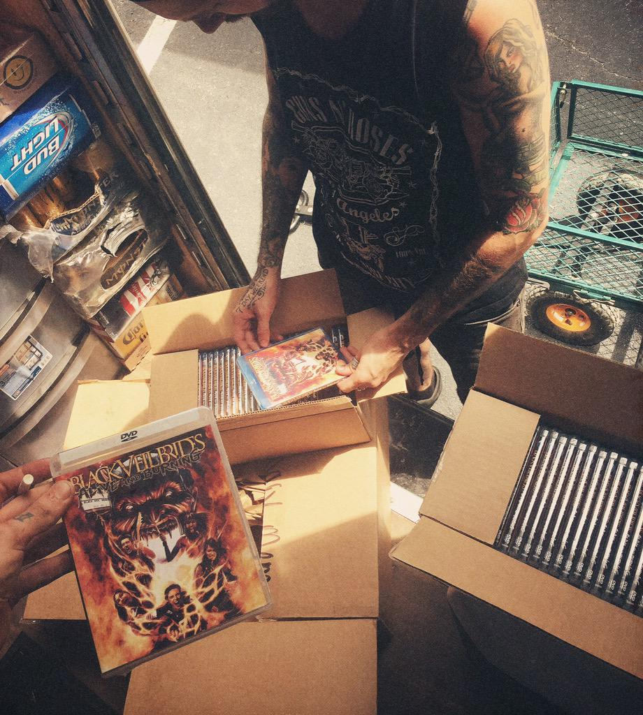 Starting TODAY pick up #AliveandBurning on DVD & Blu Ray at our Merch tent! Here's @WaywardJesseLee gettin 'em ready! http://t.co/wIJvt40bND