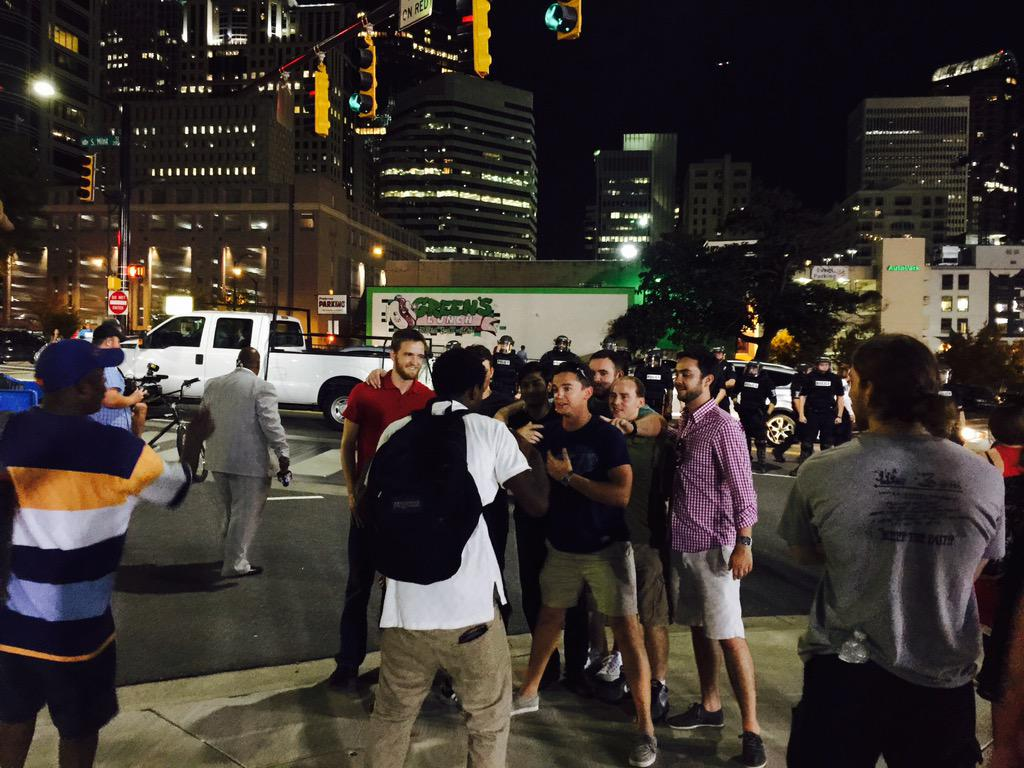 Here is your riot, #CLT. Buncha mostly white dudes mugging for pic in front of riot-ready #CMPD. #BlackLivesMatter http://t.co/gZyzhexMR8