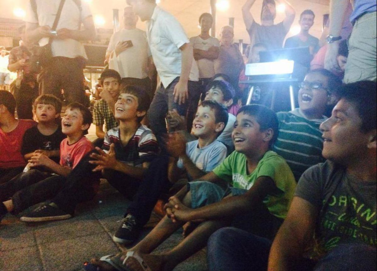 Hungarian volunteers have set up a projector showing Tom and Jerry for the refugee children.  Look at those faces! http://t.co/6SiFpGaBWZ