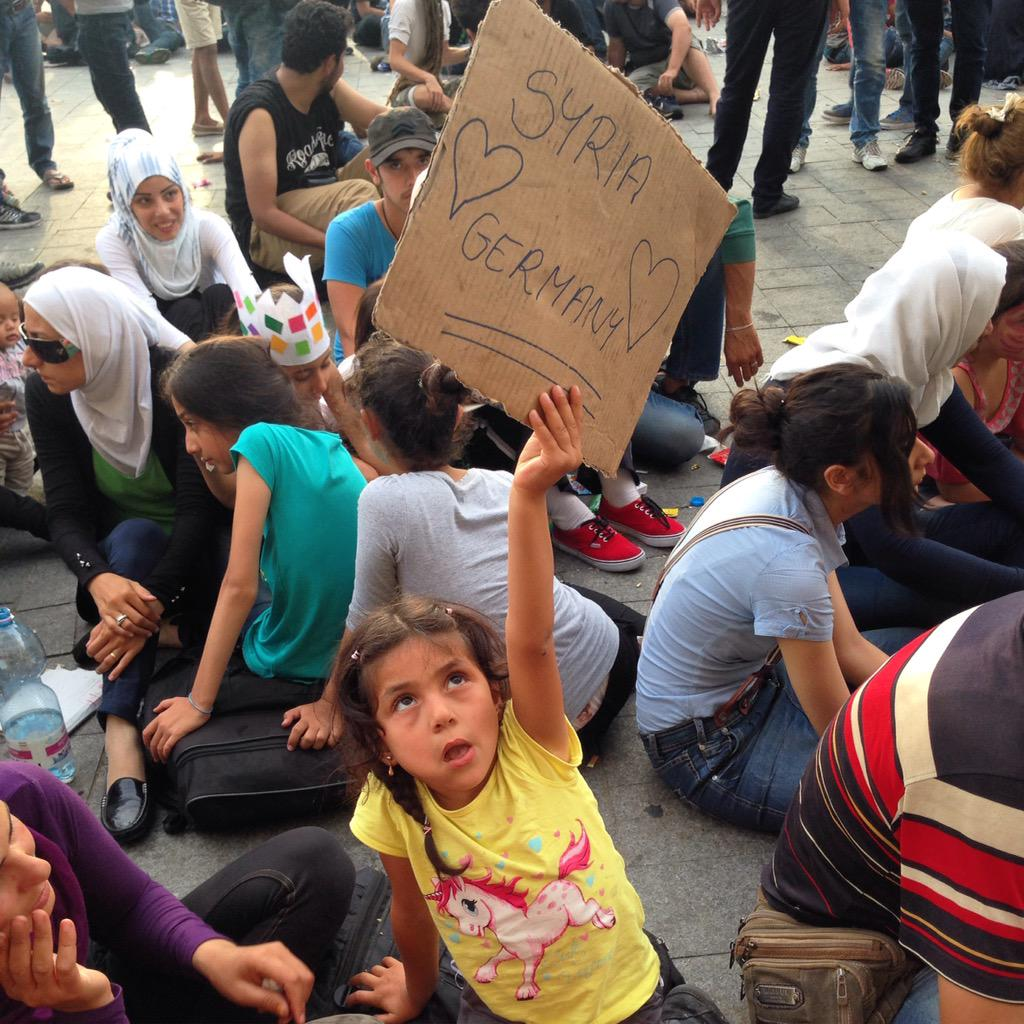 "A young #refugee at #Budapest's #Keleti Station w ""#Syria Loves #Germany"" sign. She & family trying to leave #Hungary http://t.co/l96FrQgJ14"