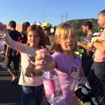 Two Hungarian girls hand out food and toys to children of refugees and migrants. A very sweet image. http://t.co/OGWe99BCSs