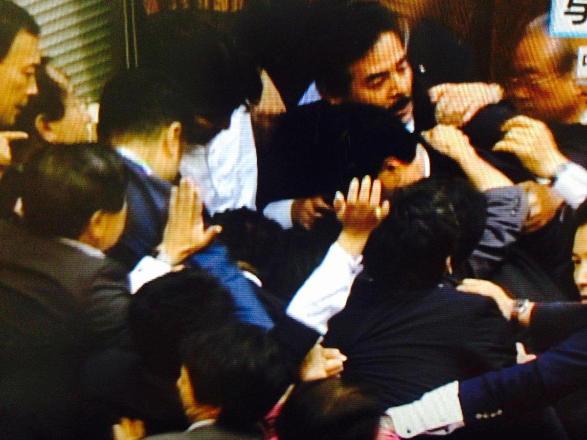 #kokkai #NHK 与党議員がスクラムを組んで委員長をガード。議事は進行しているという体裁で佐藤理事が起立のタイミングで合図を出しています。 http://t.co/QP0JpO1FQo