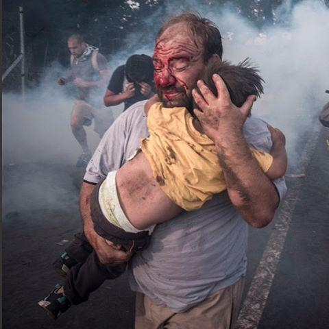 A migrant holds his child during a clash with Hungarian riot police on the Serbian border. Pic: Sergey Ponomarev http://t.co/k45P3dhC5C