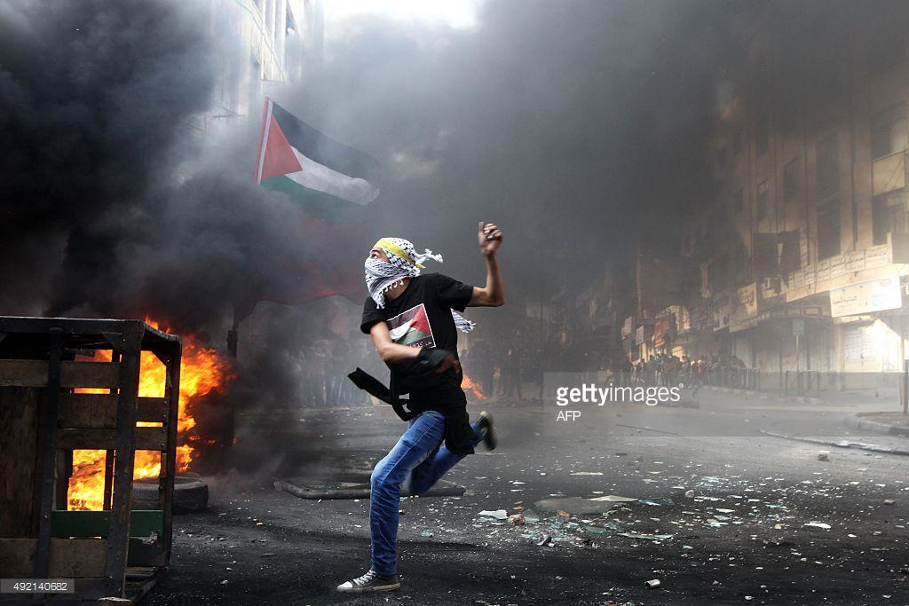 A masked Palestinian hurls rocks towards Israeli soldiers following the funeral of Mohammed Fares al-Jaabari http://t.co/RBMpza6ICL