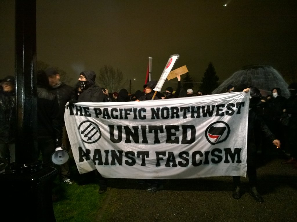 Anarchist flags flying in the rain and wind on Capitol Hill as antifascist march gets underway. #defendSeattle https://t.co/AJbk4gUFx3