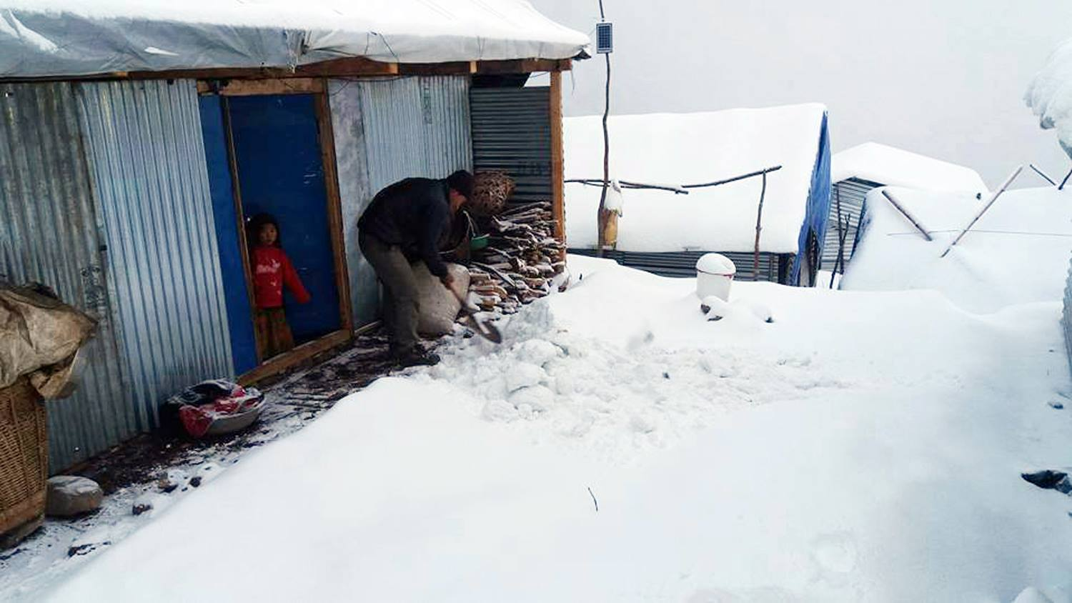 A man clears snow outside his temporary shelter in Barpak, the epicentre of April earthquake, on Saturday. Pic: RSS https://t.co/62uE1FtDTi