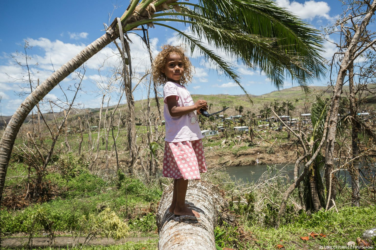 Livini, 4, from Navitilevu village, #Fiji stands on a fallen coconut tree that was uprooted by #CycloneWinston https://t.co/fePQxBcOta