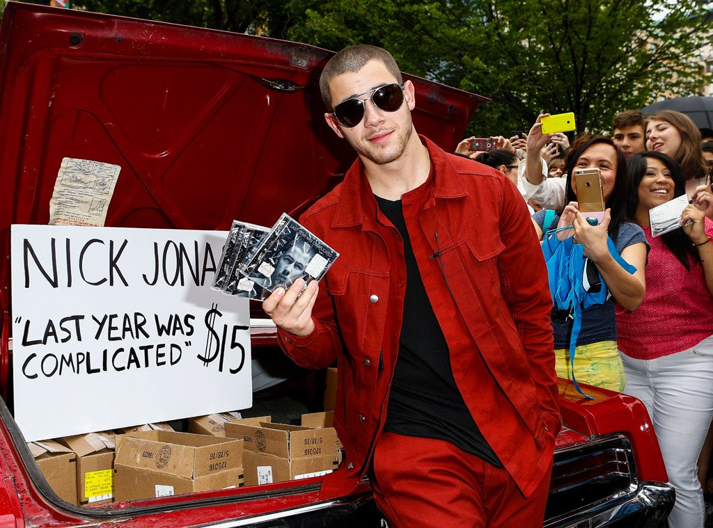 Nick Jonas selling CDs out of his trunk like a CHAMP.