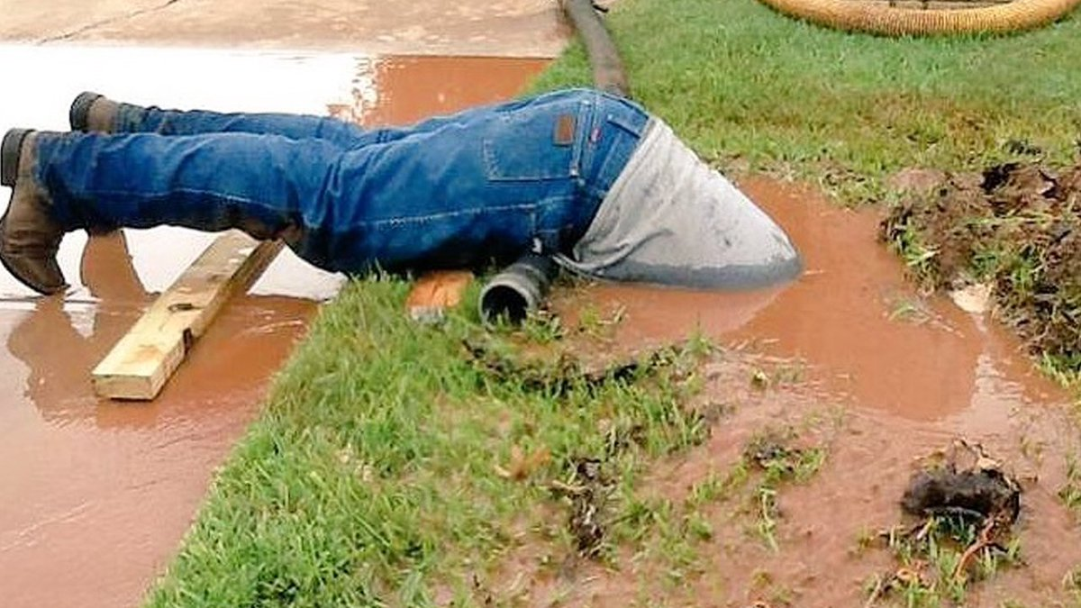 Utility worker es in head-first to fix broken water pipe photo goes viral & Utility worker es in head-first to fix broken water pipe photo ...