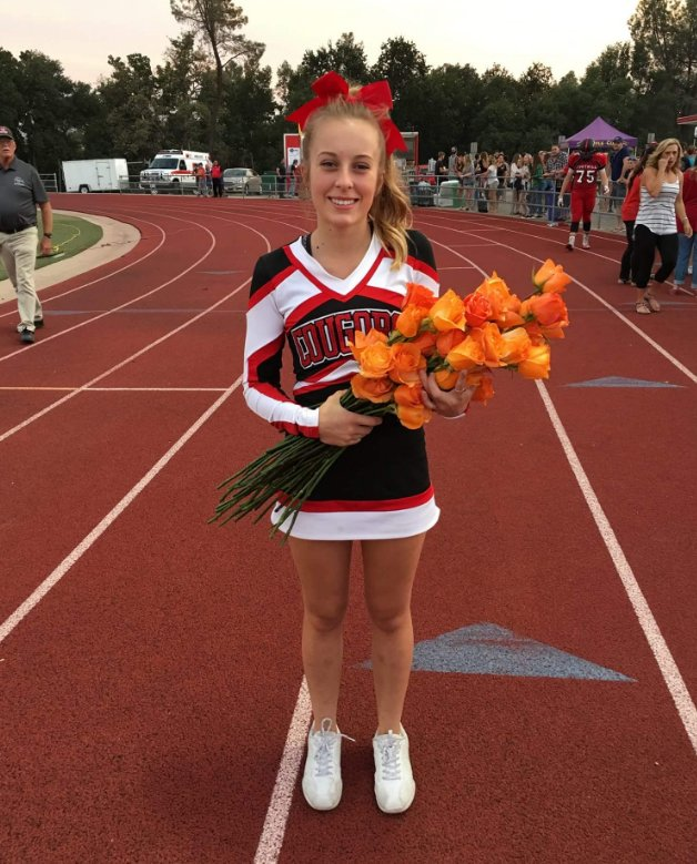 Football Players Place Roses At Feet Of Cheerleader Recently