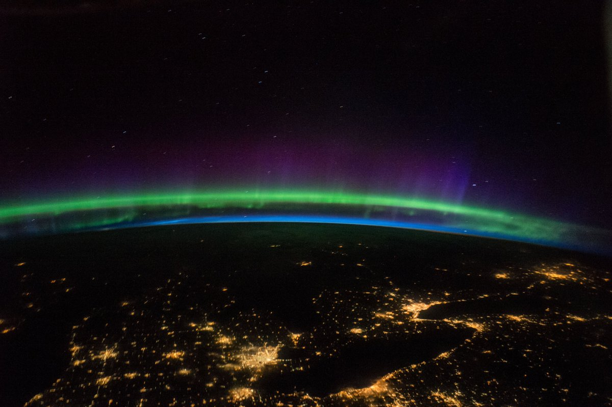 """""""Green aurora with purple highlights compliment the city lights in the Great Lakes region."""" #Exp48 https://t.co/hfsVX4sPQd"""