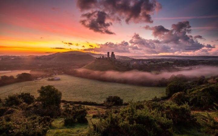 """في ساعات الصباح الأولى يغطي الضباب أرجاء مدينة """"دورست"""" جنوب إنجلترا؛ وتظهر في الأفق القلعة التاريخية """"كورف"""". الصورة: Matthew Pinner https://t.co/YsafqnP28u"""