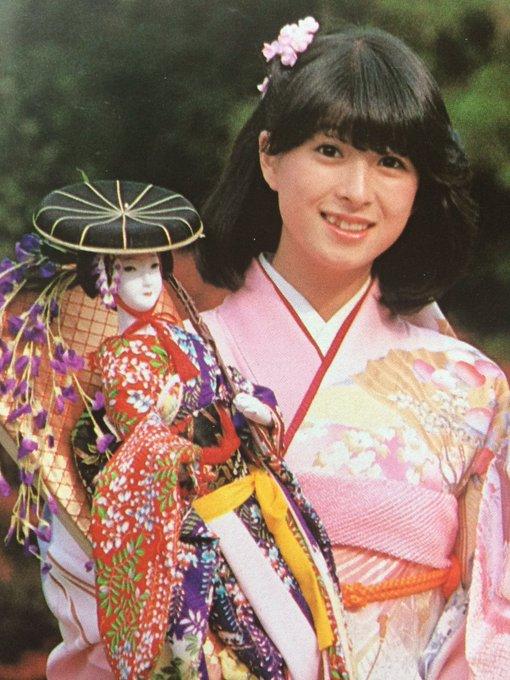 桃色の着物を着て綺麗な人形を手に持つ河合奈保子