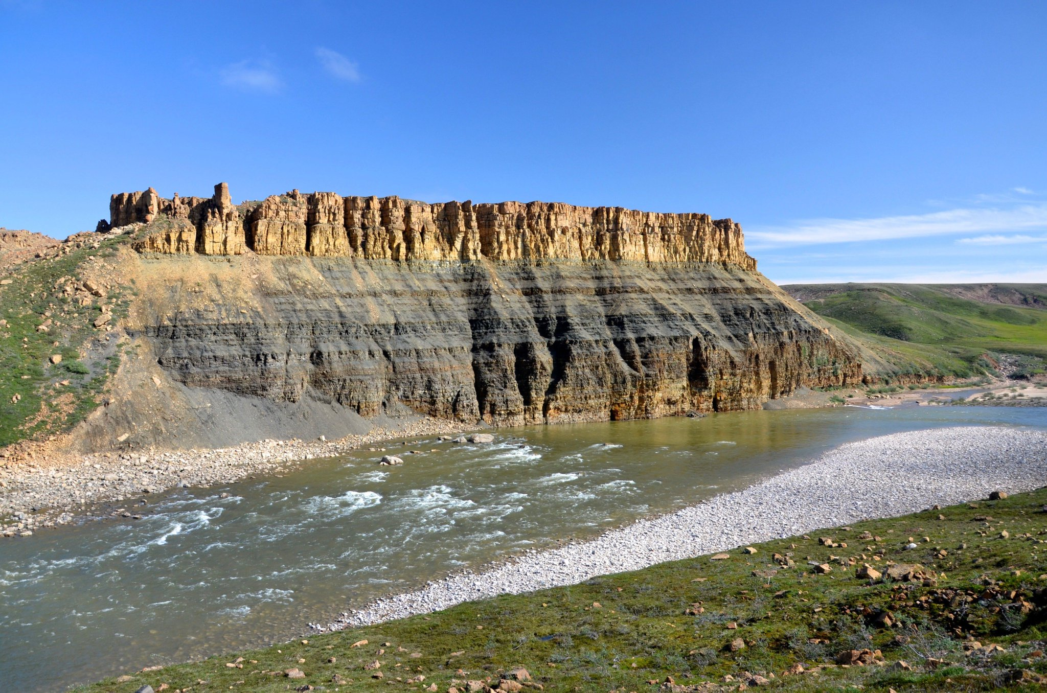 This beautiful exposure, located on the Hornaday River in Tuktut Nogait National Park, NWT, is about 80 m thick and comprises marine quartz arenite grading upward into shales abruptly but conformably overlain by orange-weathering stromatolitic dolostone. #PhotoOfTheWeek https://t.co/E39sTiBJ44