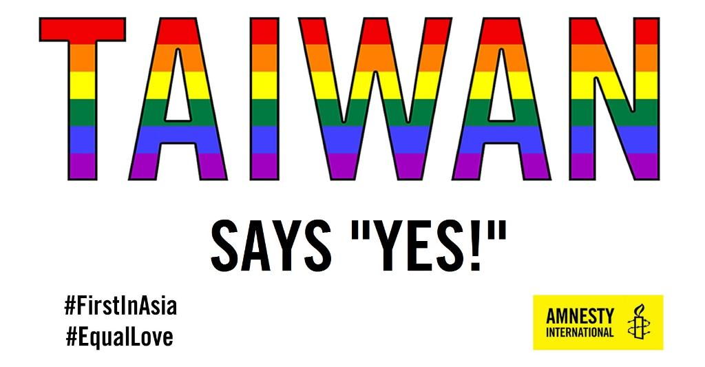 "Image is text. Taiwan in large font against a white backdrop. The colors of the rainbow flag fill in the name of the country. Under Taiwan appears ' Says ""Yes!"" ' Lower left appears to hashtags: FirstInAsia and EqualInLove Amnesty International logo appears in bottom right."