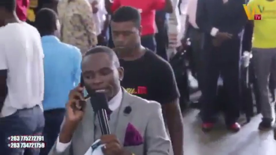 Bizarre moment African priest tries to claim he is on the phone to GOD mid-sermon