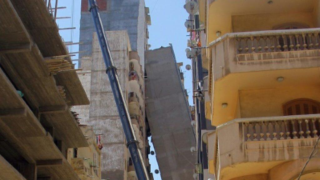 Apartment block in Egypt tilts across street