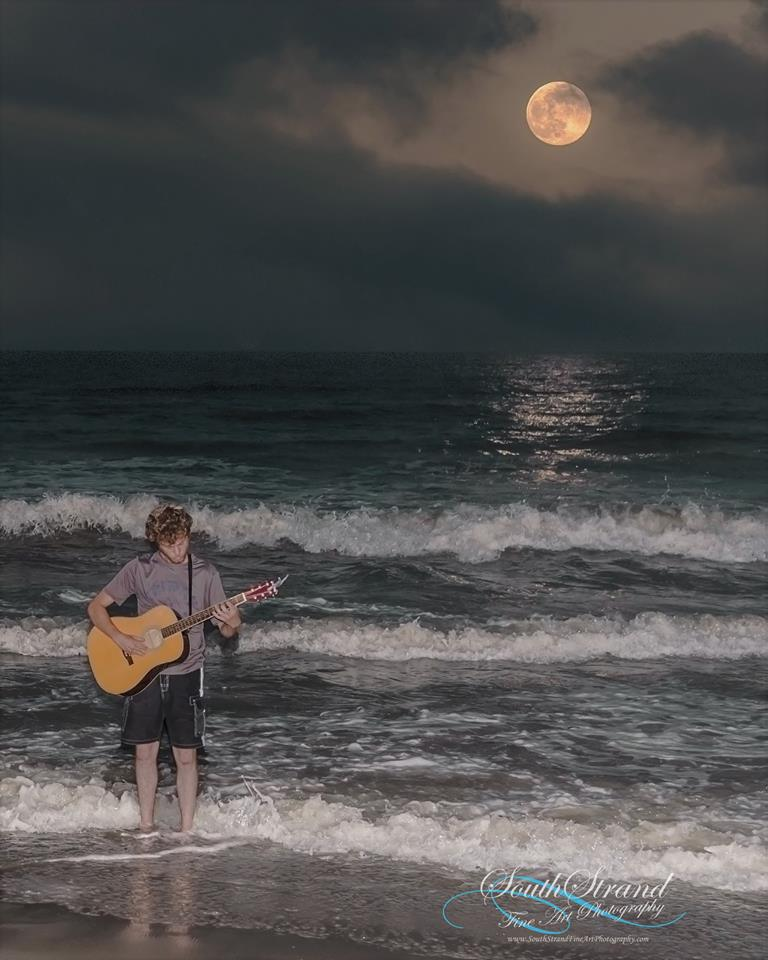 Photographer seeks identity of mystery musician captured performing by moonlight
