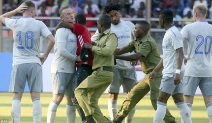 Tanzanian soccer fan sneaks past tight security to hug Wayne Rooney