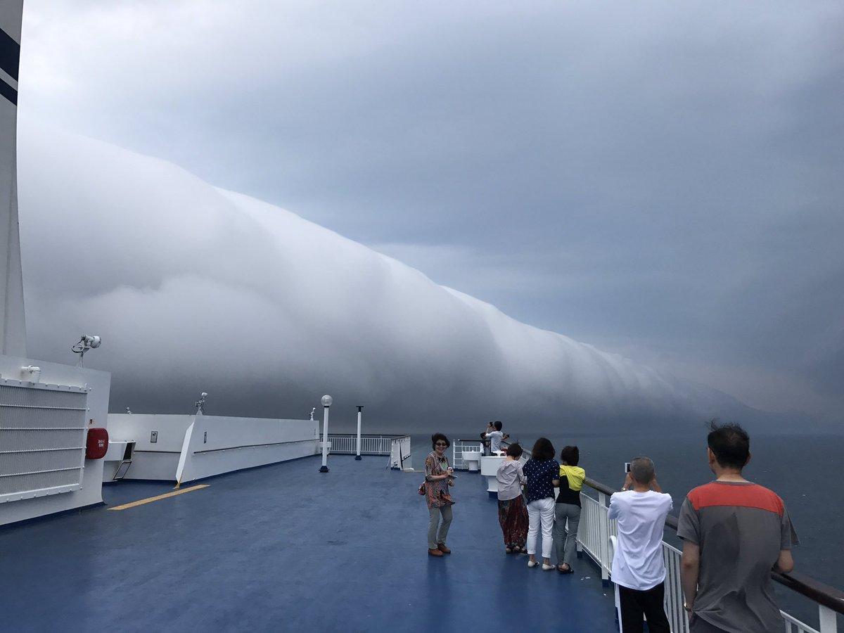 フェリーの甲板で。怪しの雲が出てて、みんな写真を撮ってる。