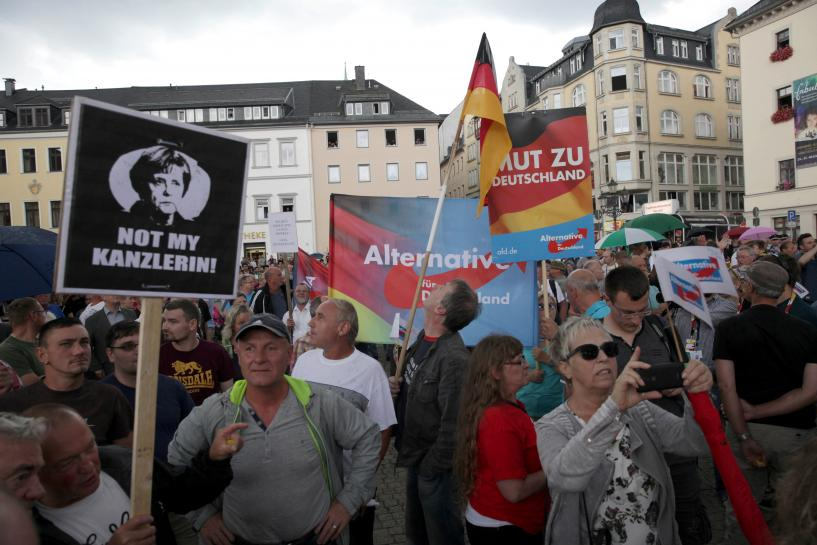 Merkel, called 'traitor', defends refugee stance in rowdy east Germany