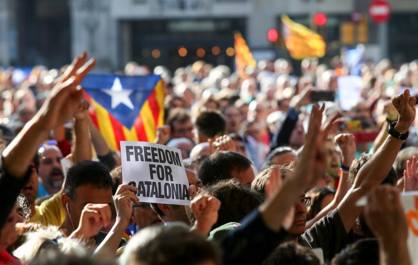 Spain police raid Catalonia government offices, arrest junior minister