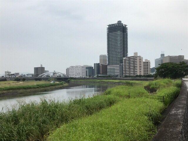 「夏目友人帳 陸」第4話「違える瞳」の聖地巡礼で熊本市内、白川沿いの歩道と辛島電停。中央の高いビルは、近年完成したものだ