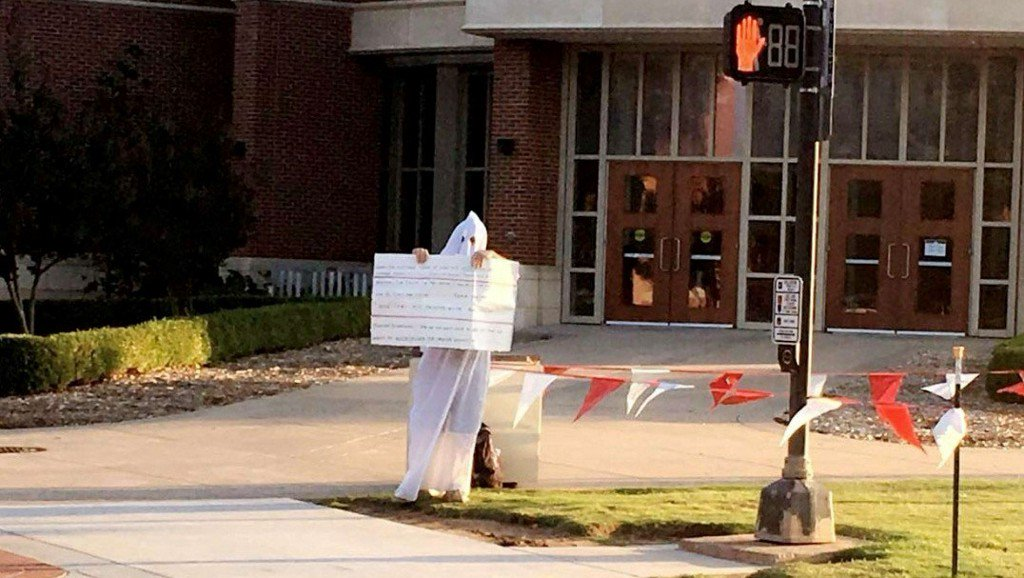 Man seen on college campus wearing white hood, carrying sign with racist comments