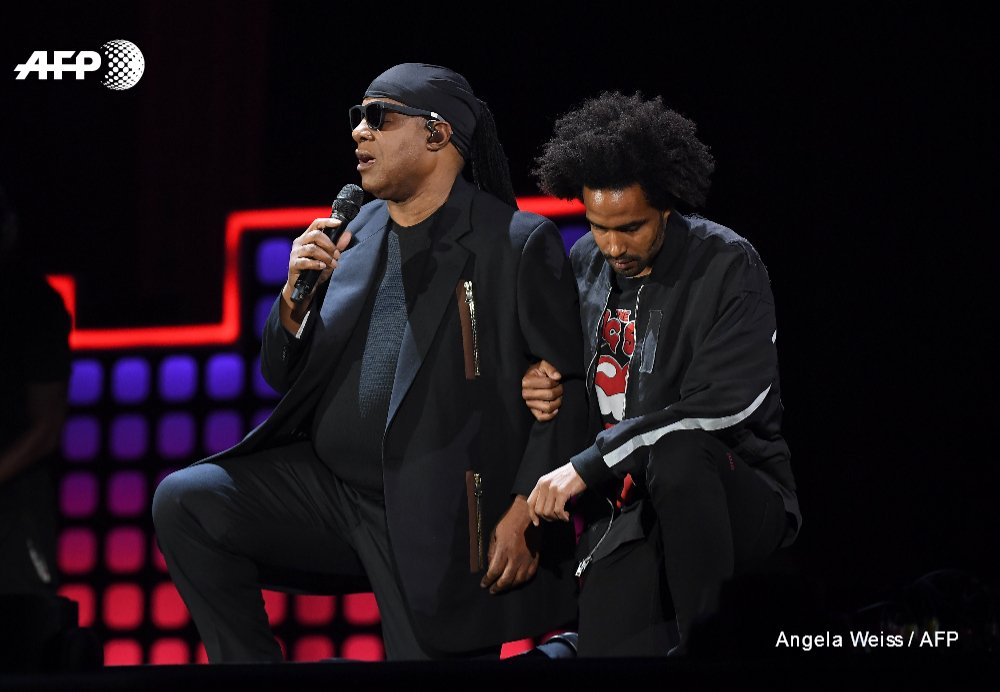 Stevie Wonder kneels before a packed New York festival in a protest for peace