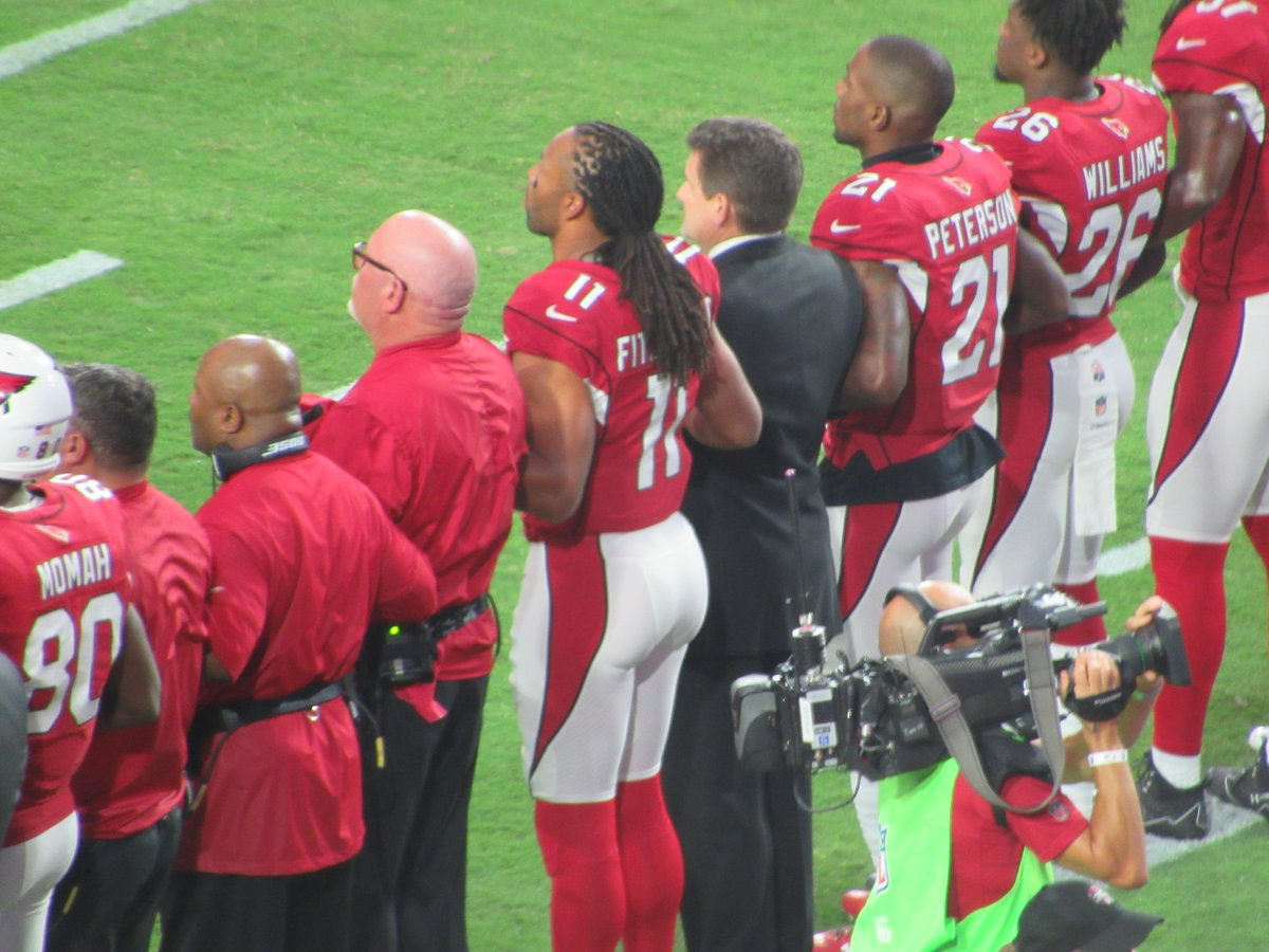 Larry Fitzgerald locks arms with coach Bruce Arians and team president...