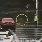 Kind driver in China tosses umbrella to traffic cop on duty in the rain