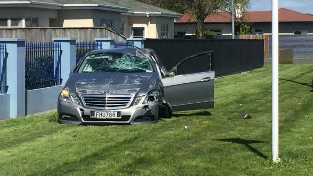 One man seriously injured when car flips in front of Palmerston North school